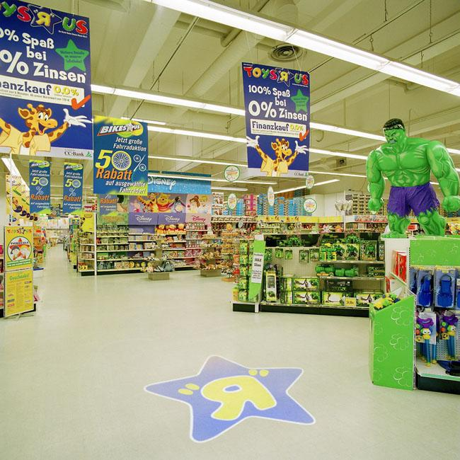 "The Toys ""R"" Us logo projected onto the floor"