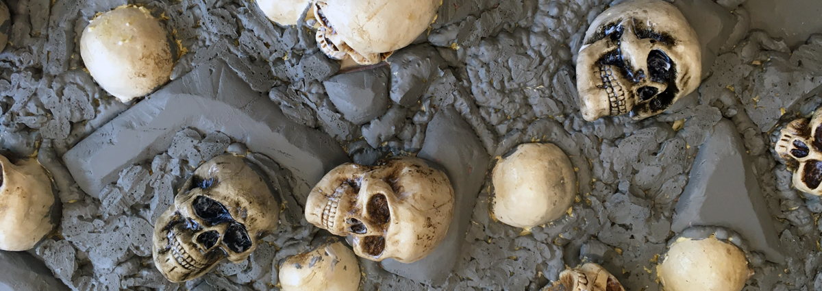 White skulls are embedded into a grey foam wall to create durable Halloween scenery.